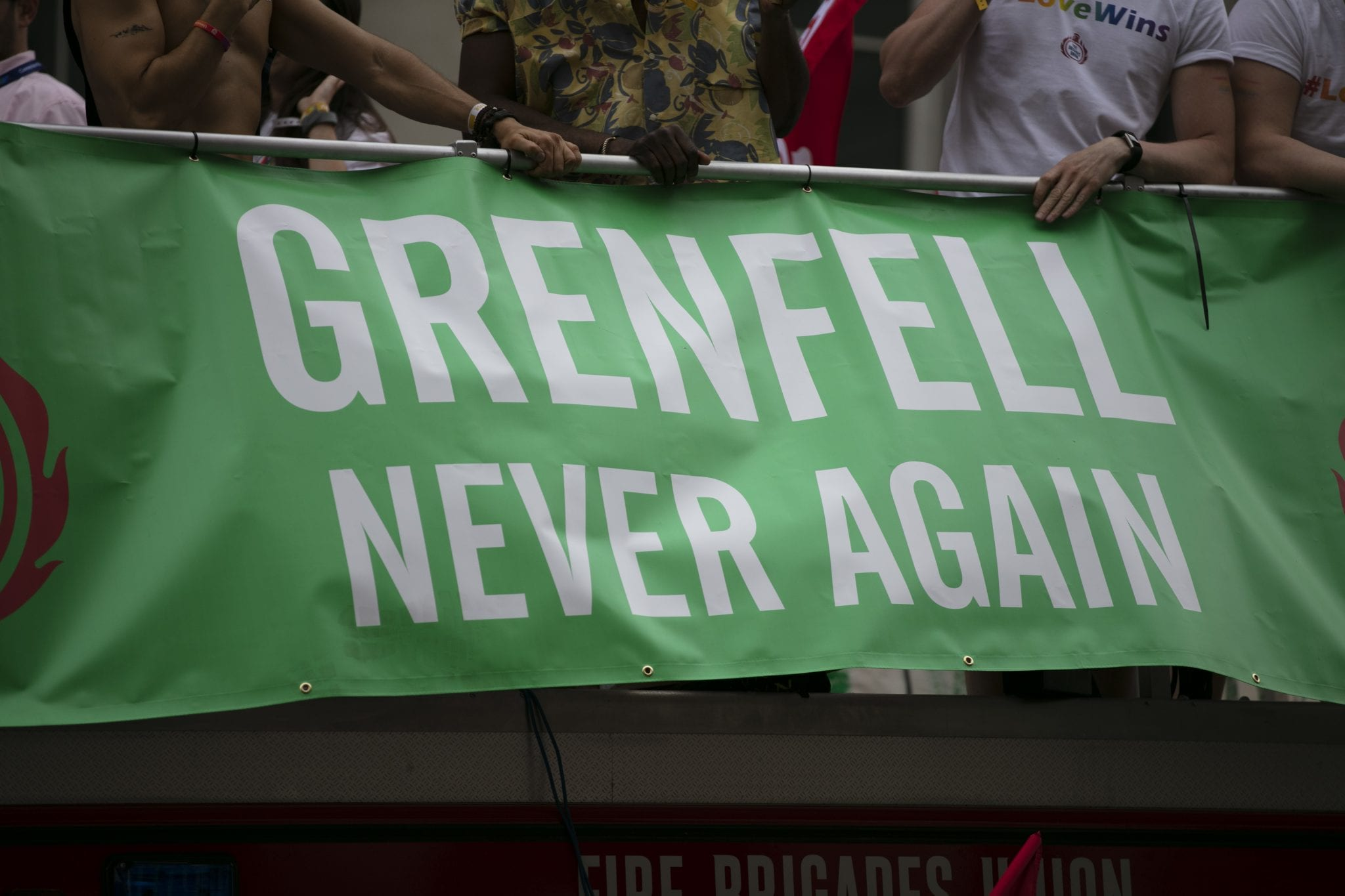 LONDON, UK – July 6th 2019: People hold a Grenfell never again sign in memory of the genfell tower disaster